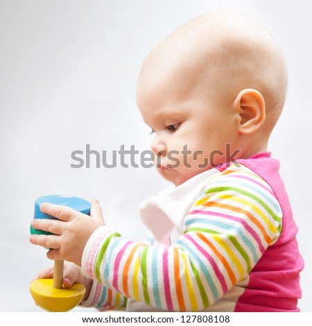Little baby plays with wooden toy, closeup portrait