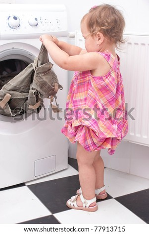 little baby reaching for the washed things out of the washing machine