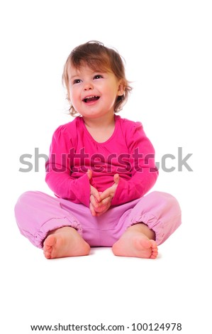 little baby sitting and smiling. pink clothing. isolated on white