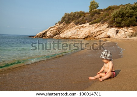 Little baby sitting on the beach and enjoying sea waves