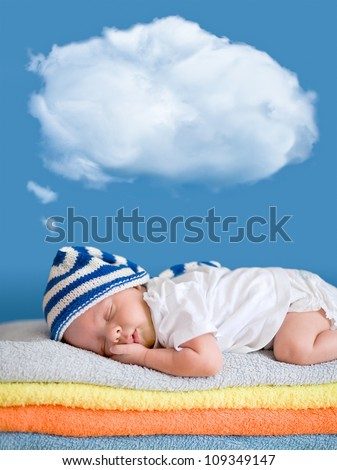 Little baby sleeping on stack of colorful towels with a dreaming balloon above