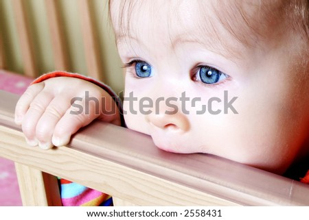 Little Baby standing in crib bitting on rail