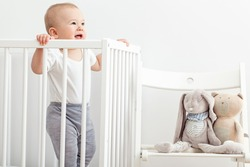 Little baby standing in his crib.