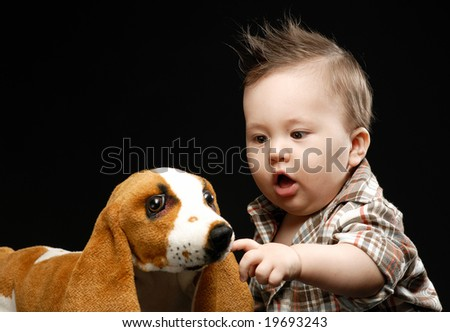 Little baby touching stuffed dog