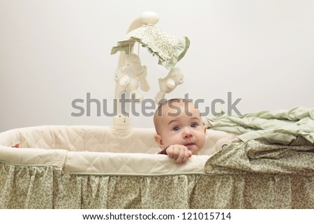 Little baby trying to get out from the crib