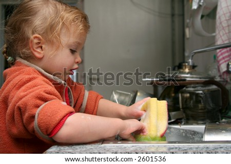 Little baby washing the dishes in the kitchen