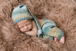 Little baby weared in light blue-yellow knitted beanie and pants sweetly sleeping on the light brown soft coverlet