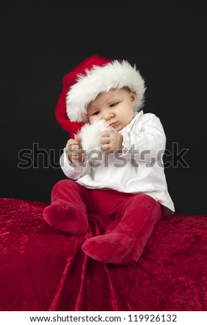 little baby with christmas hat, sitting on a big red pillow
