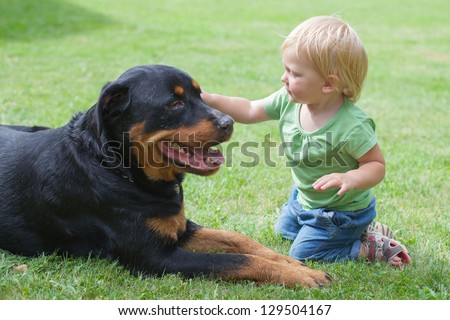 Little baby with dog on a grass