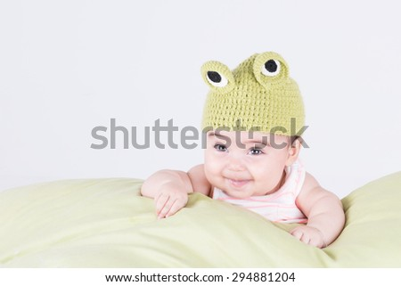 Little baby with frog hat smiling and looking up on pillow