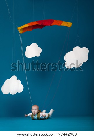 Little baby with the parachute on blue background
