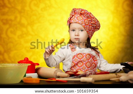 Little baker or cook girl cuts dough for cookies on kitchen with form