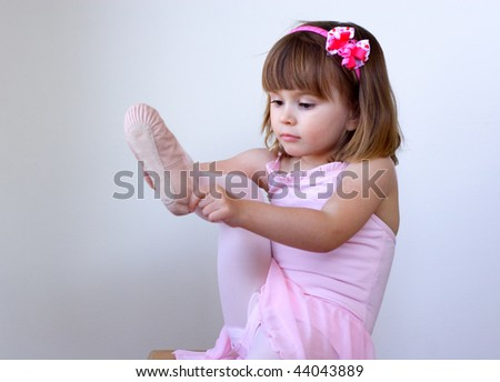 Little ballerina dancer putting on her shoe