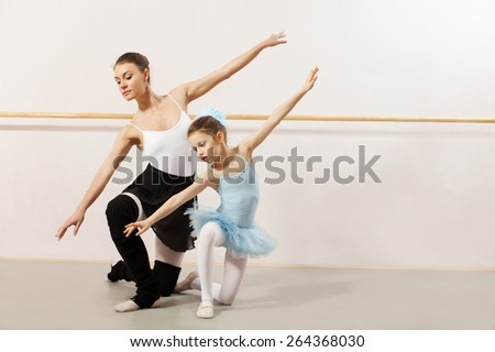 Little ballerina dancing with ballet teacher in dance studio. They both wearing a white tutu and leotard