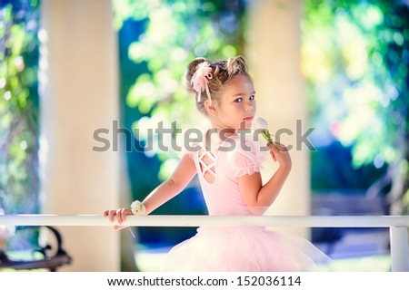 Little ballerina girl doing ballet bar exercises with flower on her hand at beautiful garden background
