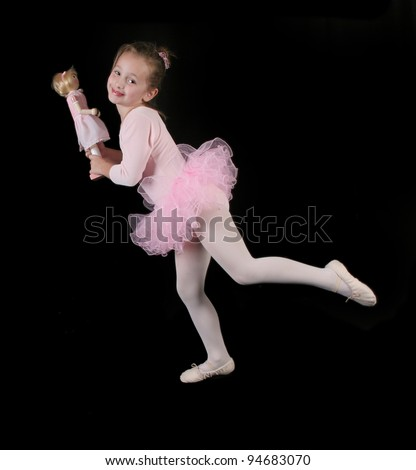 Little Ballerina Girl in Pink Tutu dancing with her Doll on Black Background