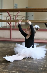 little ballerina girl performs exercises sitting on the floor in a ballet class