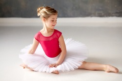 Little ballerina in pink leotard and white tutu, studio atmosphere, bright atmosphere
