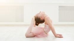 Little ballerina in split on floor, copy space. Smiling baby girl dreaming to become professional ballet dancer, classical dance school