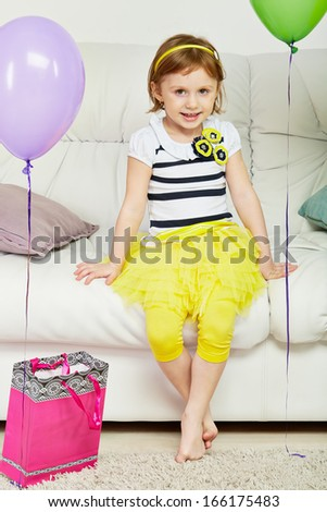 Little barefooted girl sits on big sofa in room with carpet on floor, paper gift bag and birthday air balloons