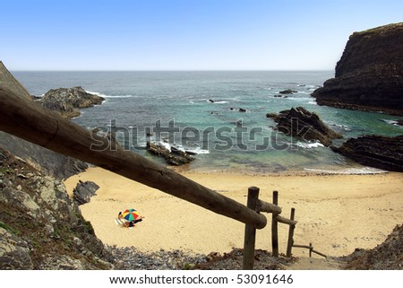 little beach with wooden stairway and surrounded by rocky cliffs