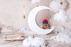 Little bear Pilot on the moon. Interior home decorated with moon (month), stars, clouds and a wooden plane, vintage decor. Wooden plane. Children room. Decorative white wooden moon. Postcard.