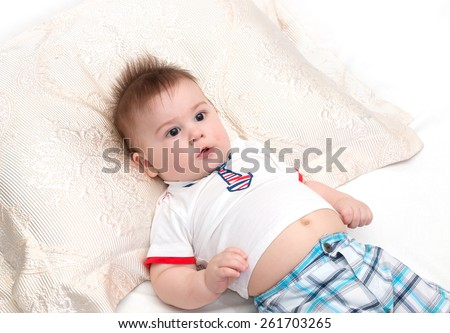 Little beautiful baby lying on pillow surprised