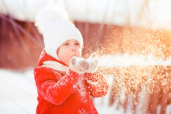 Little beautiful, blue-eyed cheerful girl 4 - 5 years in a red coat and white winter cap with a pompon walks in winter playing with snow and laughing next to the Christmas tree (fir tray)