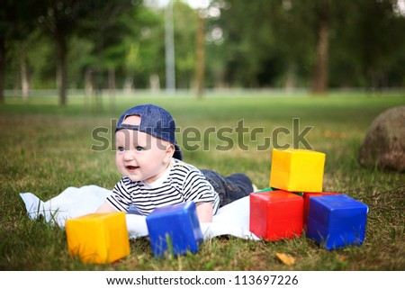 little beautiful boy playing with blocks in summer park