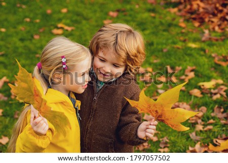 Little beautiful couple on falling autumn maple leaves background. Kids love concept. Child friendship and kindness Photo stock ©