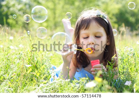 little beautiful girl blowing soap bubbles - stock photo