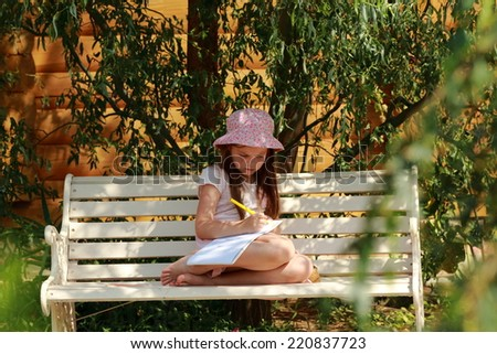 Little beautiful girl child draws with crayons in the album outdoors