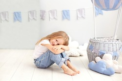 Little beautiful girl in a white T-shirt and jeans sits on the background of a decorative balloon. The child plays in the children's room. The concept of childhood, travel. birthday holiday decoration