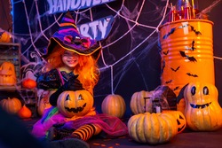 Little beautiful girl in a witch costume celebrates Happy Halloween party in interior with pumpkins.