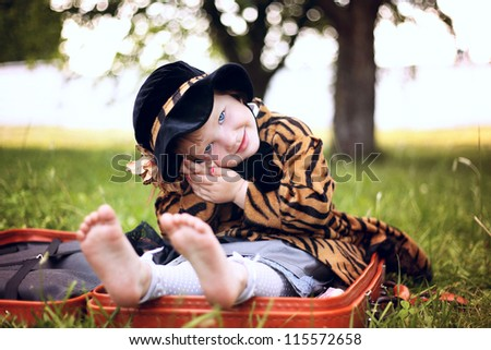 little beautiful girl in hat and cloak  hiding in suitcase in autumn park