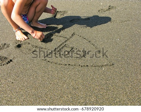 Little beautiful girl in hood draws in sand image of house. #678920920