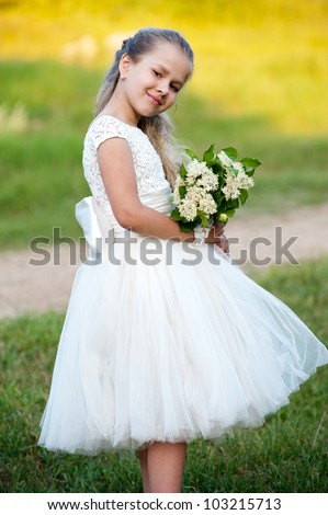Little beautiful girl in the fashion dress in  the park