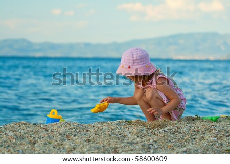 Little beautiful girl in the hat playing on the beach with a cutter. Greece, Halkidiki, kassandra.