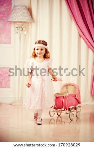 Little beautiful girl play with pram