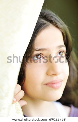 little beautiful girl sitting at window and holding curtain, portrait