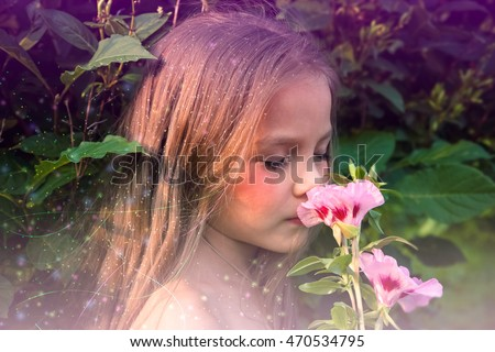 Little beautiful girl smelling a flower #470534795