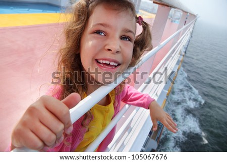 Little beautiful girl stands on board of large ship, clings to railing and laughs