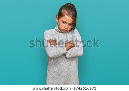 Little beautiful girl wearing casual turtleneck sweater skeptic and nervous, disapproving expression on face with crossed arms. negative person.  Stock foto ©