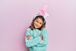 Little beautiful girl wearing cute easter bunny ears happy face smiling with crossed arms looking at the camera. positive person.