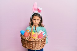 Little beautiful girl wearing cute easter bunny ears holding wicker basket with colored eggs skeptic and nervous, frowning upset because of problem. negative person.