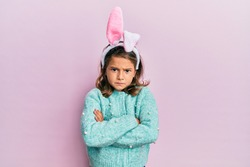 Little beautiful girl wearing cute easter bunny ears skeptic and nervous, disapproving expression on face with crossed arms. negative person.