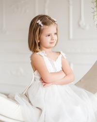Little beautiful girl with a caret in a white dress on a white ring