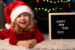 little beautiful girl with Santa Claus hat and red Christmas dress is lying under the Christmas tree and laughing, next to a black Board and white letters text happy new year 2021