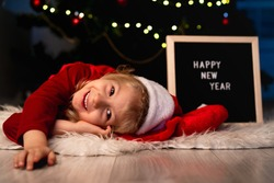 little beautiful girl with Santa Claus hat and red Christmas dress is lying under the Christmas tree and laughing, next to a black Board and white letters text happy new year