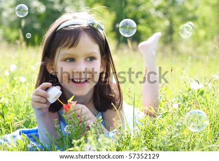 little beautiful happy girl blowing soap bubbles